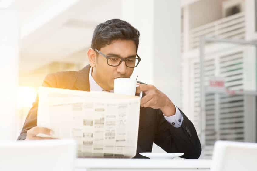Business People Drinking Hot Coffee And Reading Newspaper At Caf