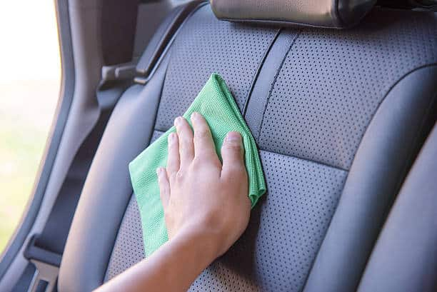 Hand Cleaning The Car Interior With Green Microfiber Cloth